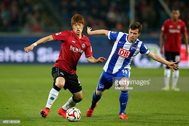 Hiroki Sakai of Hannover 96 is challenged by Valentin Stocker of Hertha BSC during the Bundesliga match between Hannover 96 and Hertha BSC at...