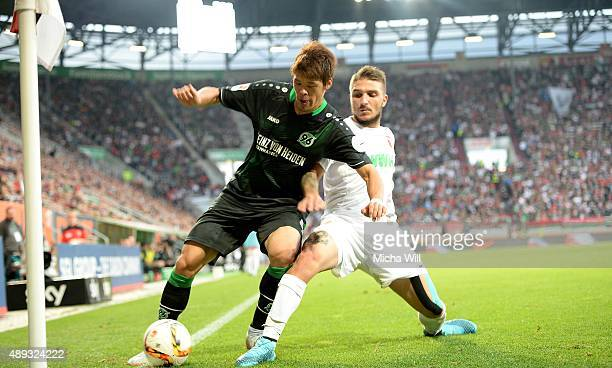 Hiroki Sakai of Hannover and Konstantinos Stafylidis of Augsburg tussle for the ball during the Bundesliga match between FC Augsburg and Hannover 96...