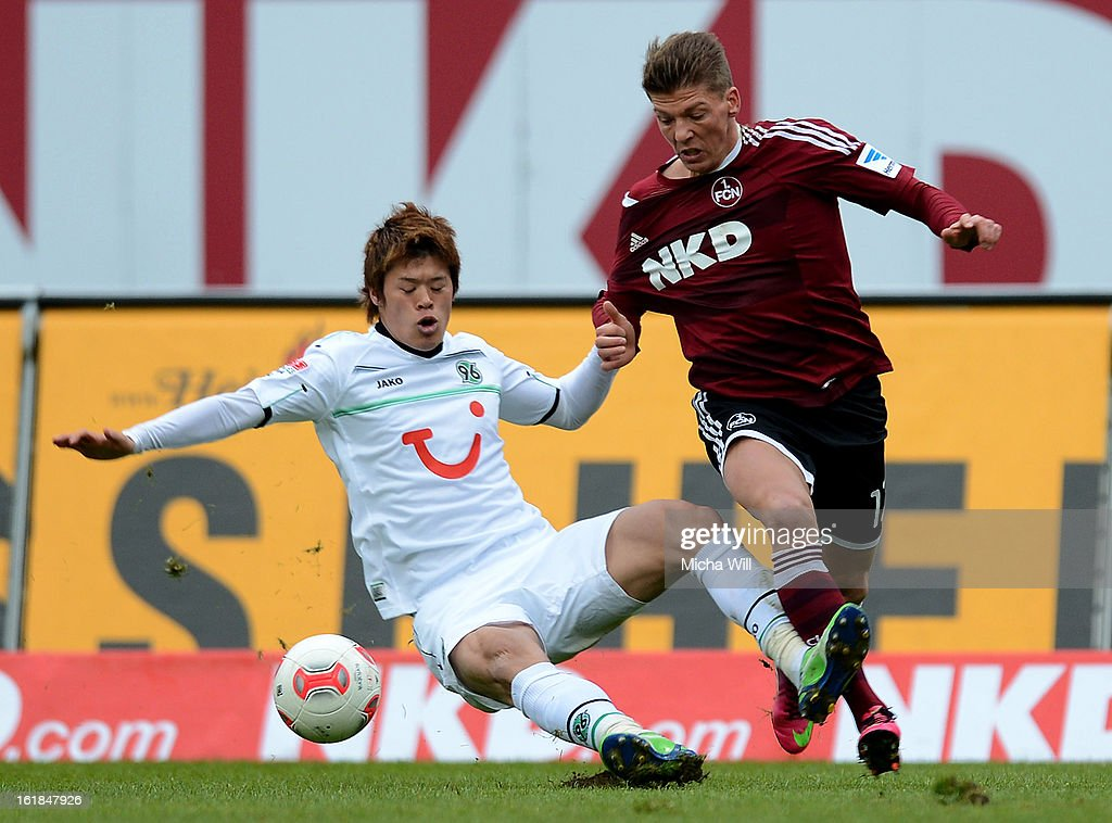 Hiroki Sakai of Hannover (L) falls whilst challenging Mike Frantz of Nuernberg during the Bundesliga match between 1. FC Nuernberg and Hannover 96 at Grundig-Stadion on February 17, 2013 in Nuremberg, Germany.
