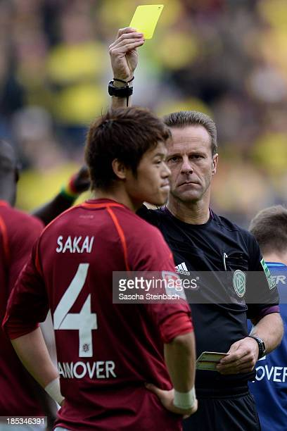 Hiroki Sakai of Hannover is booked yellow card by referee Peter Gagelmann during the Bundesliga match between Borussia Dortmund and Hannover 96 at...