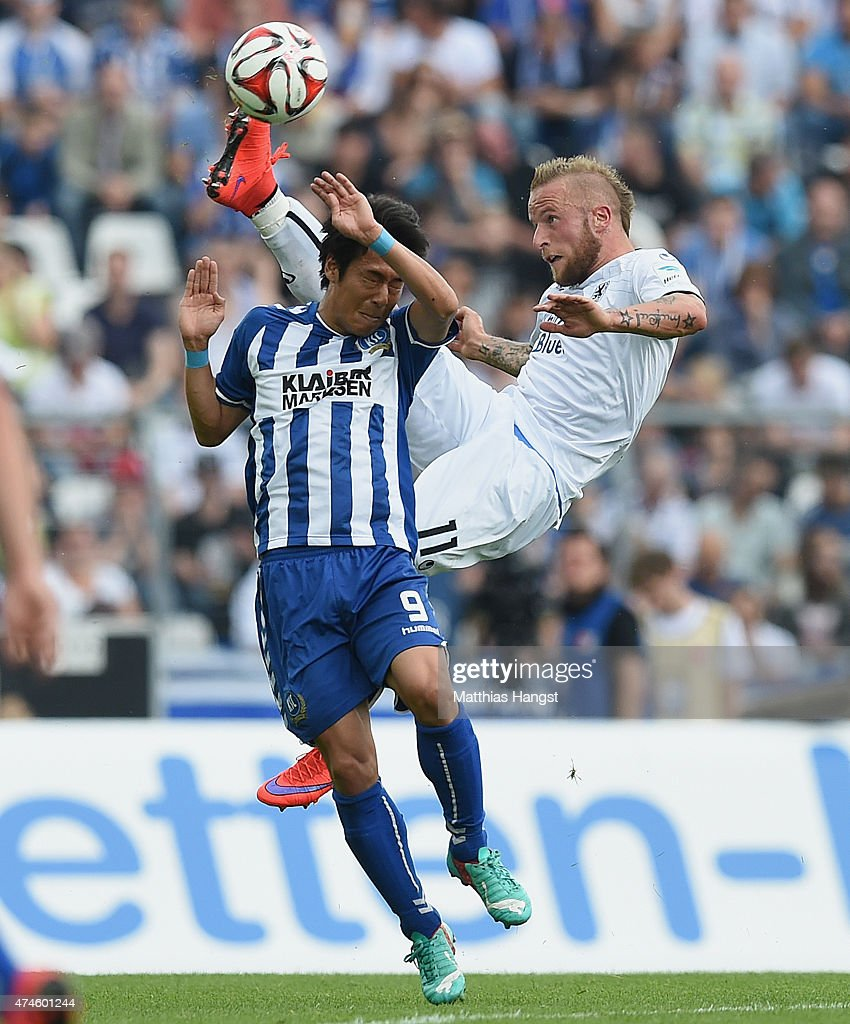 Hiroki Yamada of Karlsruhe and Daniel Adlung of 1860 Muenchen compete for the ball during the Second Bundesliga match between Karlsruher SC and 1860...