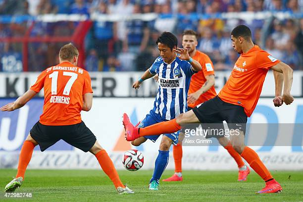 Hiroki Yamada of Karlsruhe is challenged by Hanno Behrens and Leon Balogun of Darmstadt during the Second Bundesliga match between Karlsruher SC and...