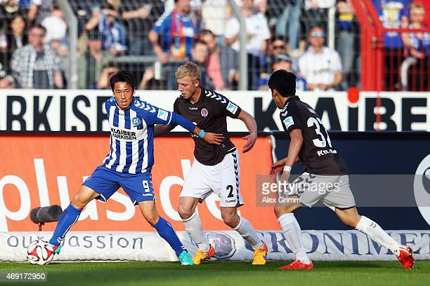 Hiroki Yamada of Karlsruhe is challenged by Julian Koch and Kyoung Rok Choi of St Pauli during the Second Bundesliga match between Karlsruher SC and...