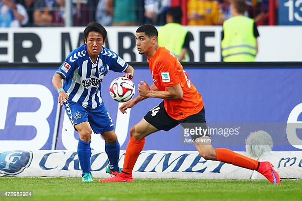 Hiroki Yamada of Karlsruhe is challenged by Leon Balogun of Darmstadt during the Second Bundesliga match between Karlsruher SC and SV Darmstadt 98 at...