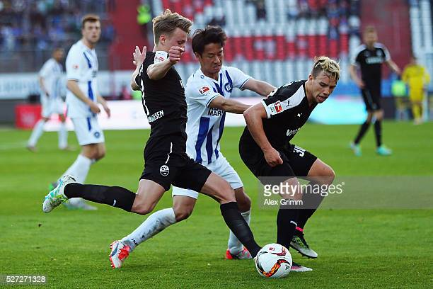Hiroki Yamada of Karlsruhe is challenged by Marco Thiede and Thomas Pledl of Sandhausen during the Second Bundesliga match between Karlsruher SC and...