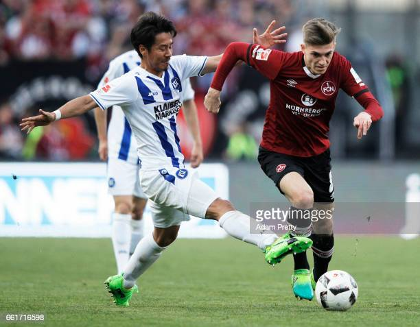 Hiroki Yamada of Karlsruher SC challenged L Hufnagel of 1FC Nuernberg during the Second Bundesliga match between 1 FC Nuernberg and Karlsruher SC at...
