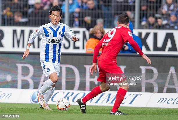 Hiroki Yamada of Karlsruher SC challenges Sven Ullrich of 1 FC Heidenheim during the second bundesliga match between Karlsruher SC and 1 FC...