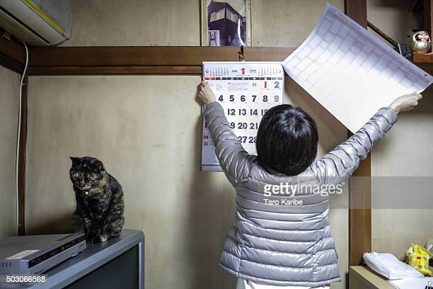 Hiroko Togawa 48 years old puts a new calender on the wall on January 1 2016 in Tokyo Japan In Japan the New Year is celebrated with a series of...