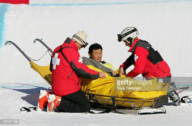 Hiroomi Takizawa of Japan is loaded onto a sled to be taken off the mountain by medical personnel after he crashed during the semifinals in the men's...
