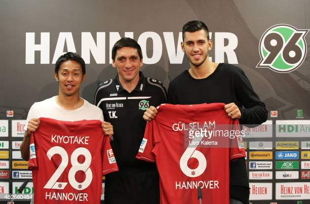 Hiroshi Kiyotake head coach Tayfun Korkut and Cheyhun Guelselam pose with their shirts during a press conference at HDI Arena on July 25 2014 in...
