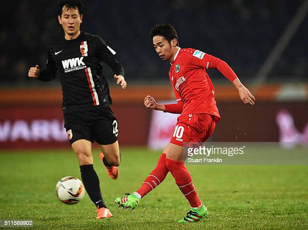Hiroshi Kiyotake of Hannover is challenged by DongWon Ji of Augsburg during the Bundesliga match between Hannover 96 and FC Augsburg at HDIArena on...