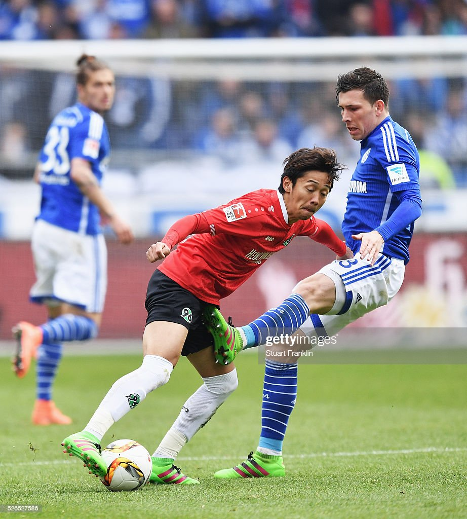 Hiroshi Kiyotake of Hannover is challenged by Pierre-Emile H��jbjerg of Schalke during the Bundesliga match between Hannover 96 and FC Schalke 04 at the HDI Arena on April 30, 2016 in Hanover, Lower Saxony.