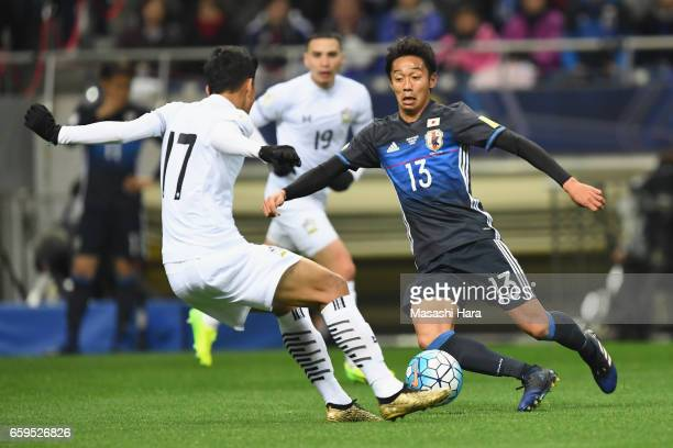 Hiroshi Kiyotake of Japan and Tanaboon Kesarat of Thailand compete for the ball during the 2018 FIFA World Cup Qualifier match between Japan and...