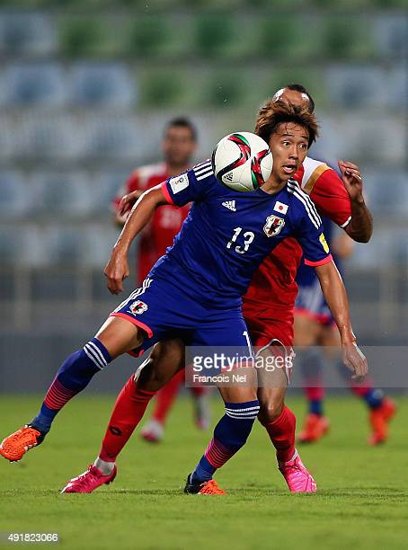 Hiroshi Kiyotake of Japan battles for the ball with Osama Omari of Syria during the 2018 FIFA World Cup Asian Group E qualifying match between Syria...