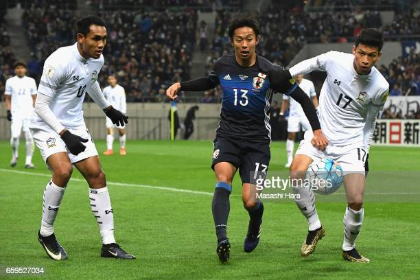 Hiroshi Kiyotake of Japan competes for the ball agaiant Tanaboon Kesarat and Teerasil Dangda of Thailand compete for the ball during the 2018 FIFA...
