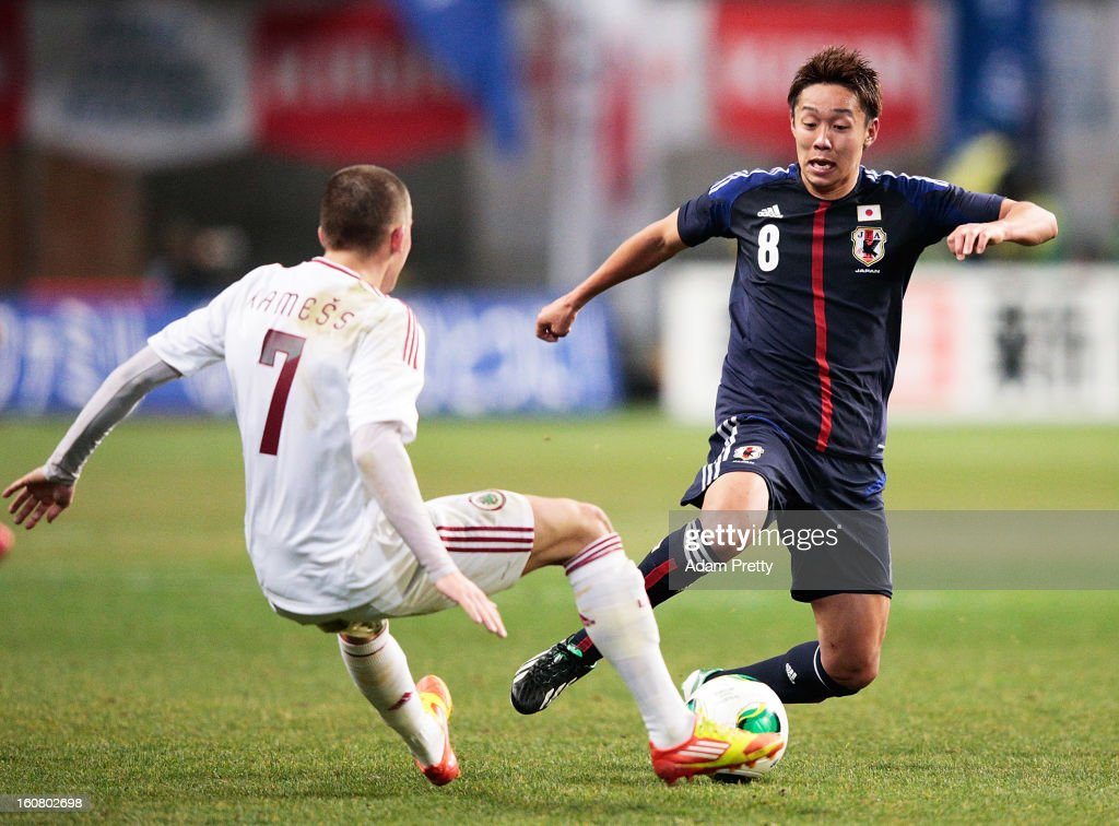 Hiroshi Kiyotake of Japan is tackled during the international friendly match between Japan and Latvia at Home's Stadium Kobe on February 6, 2013 in Kobe, Japan.