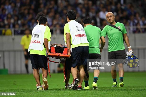 Hiroshi Kiyotake of Japanis carried off the pitch after clashing with a player of Iraq during the 2018 FIFA World Cup Qualifiers match between Japan...