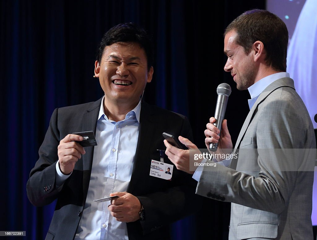 Hiroshi Mikitani, chairman and chief executive officer of Rakuten Inc., left, reacts as Jack Dorsey, chief executive officer of Square Inc. and co-founder and chairman of Twitter Inc., speaks at the New Economy Summit 2013 hosted by the Japan Association of New Economy (JANE) in Tokyo, Japan, on Tuesday, April 16, 2013. Mikitani set up the JANE in June after quitting the main business lobby Nippon Keidanren in protest over the group's support for nuclear power. Photographer: Tomohiro Ohsumi/Bloomberg via Getty Images