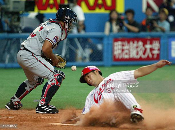 Hiroshima Carp infielder Shigenobu Shima slides home safely as catcher Johnny Estrada of the Atlanta Braves can't get the tag down in time during the...