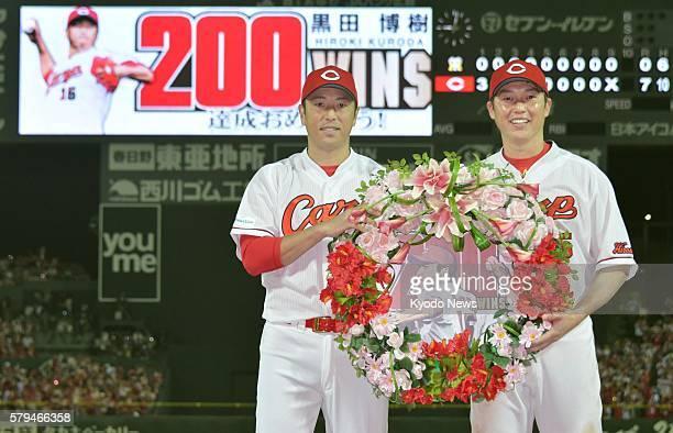 Hiroshima Carp pitcher Hiroki Kuroda is presented with a wreath of flowers by teammate Takahiro Arai in commemoration of his 200th win of his career...