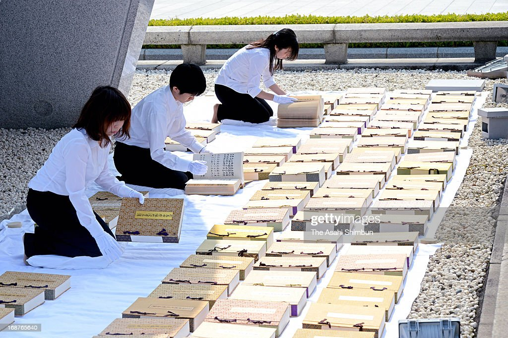 Hiroshima City officers wearing white gloves air the name books of atomic bombs victims of Hiroshima and Nagasaki to check whether there are any damages at Hiroshima Peace Memorial Park on May 15, 2013 in Hiroshima, Japan. The officers check each pages of 103 books, that recorded 280,968 victims' names and the date of death. A name book recording the victims who passed away after last year's peace memorial will be dedicated to the stone chamber located underneath the peace monument at this year's Peace Memorial on August 6.