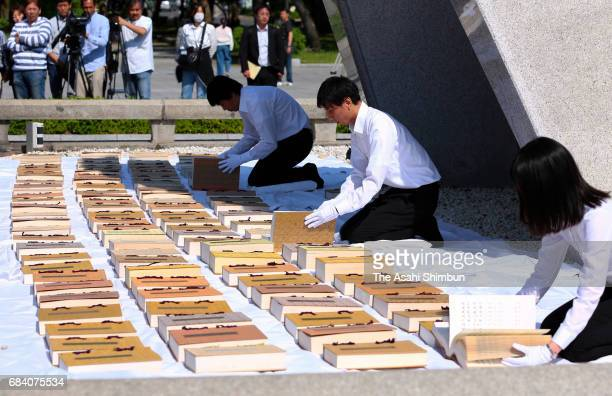 Hiroshima City officers wearing white gloves air the name books of atomic bombs victims of Hiroshima and Nagasaki to check whether there are any...