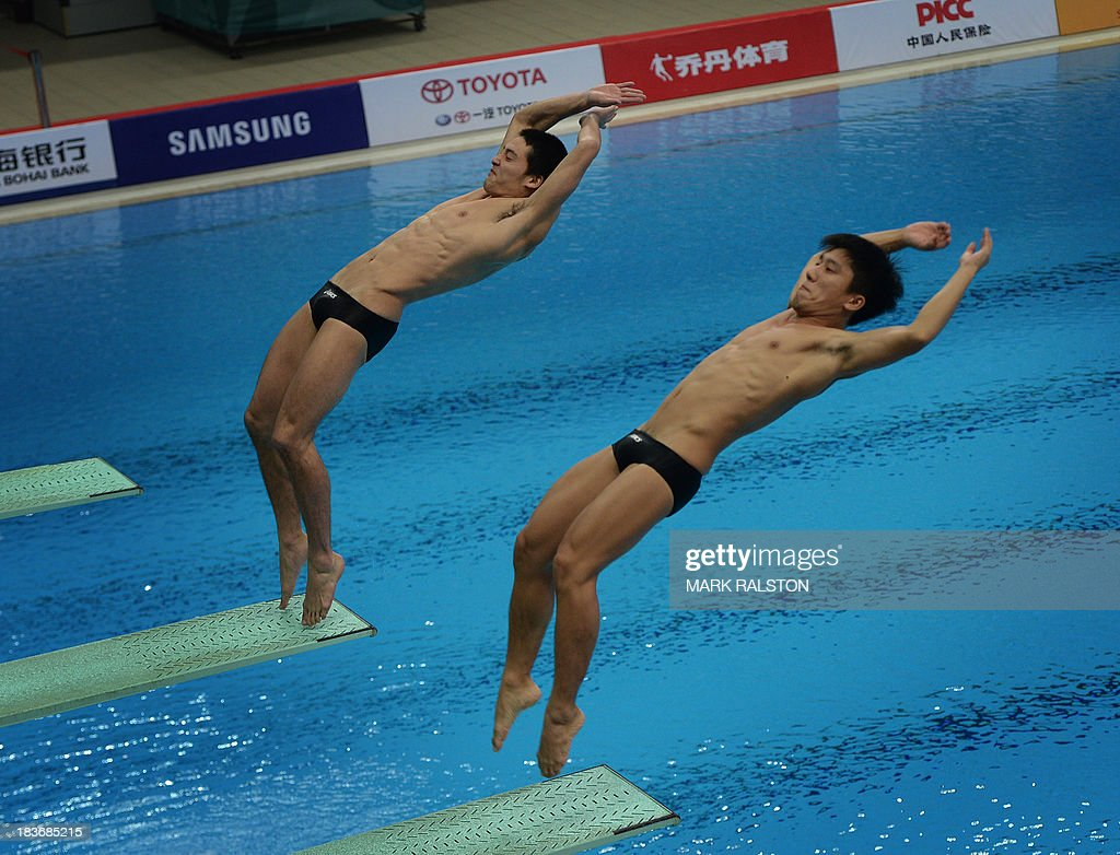 Hiroto Hasegawa (L) and Yu Okamoto (R) compete before winning gold in the Men's Synchronized 3m Springboard Final at the East Asian Games held at the Tianjin Olympic Center Diving Hall in Tianjin on October 9, 2013. The East Asian Games which are held every four years see nine countries including China, Japan, South and North Korea participating in 262 events in 22 different sports. AFP PHOTO / Mark RALSTON