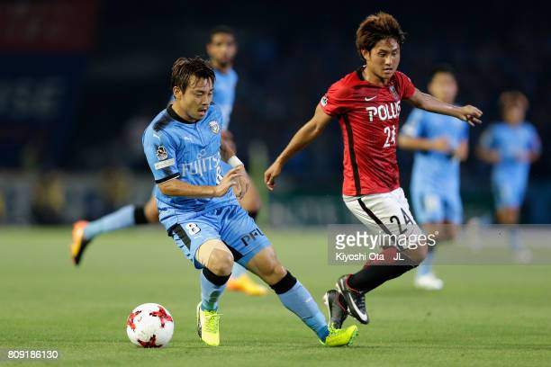 Hiroyuki Abe of Kawasaki Frontale and Takahiro Sekine of Urawa Red Diamonds compete for the ball during the JLeague J1 match between Kawasaki...