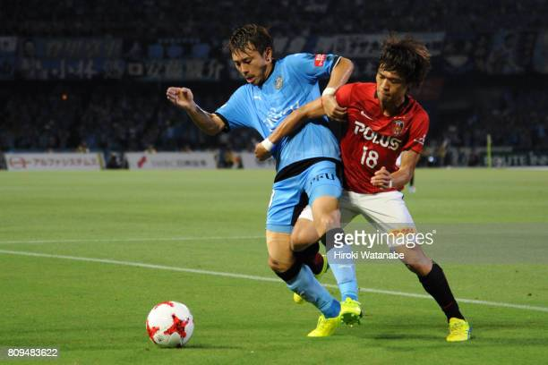 Hiroyuki Abe of Kawasaki Frontale and Yoshiaki Komai of Urawa Red Diamonds cmpete for the ball during the JLeague J1 match between Kawasaki Frontale...