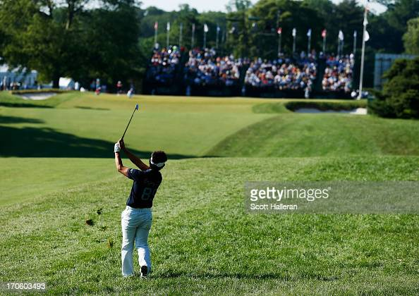 Hiroyuki Fujita of Japan hits an approach shot on the 18th hole during the continuation of Round Two of the 113th US Open at Merion Golf Club on June...