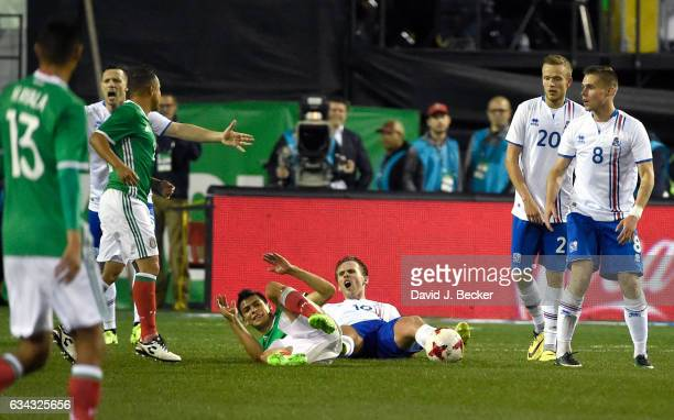 Hirving Lozano of Mexico and David Thor Vidarsson of Iceland react after a foul during the second half of their exhibition match at Sam Boyd Stadium...