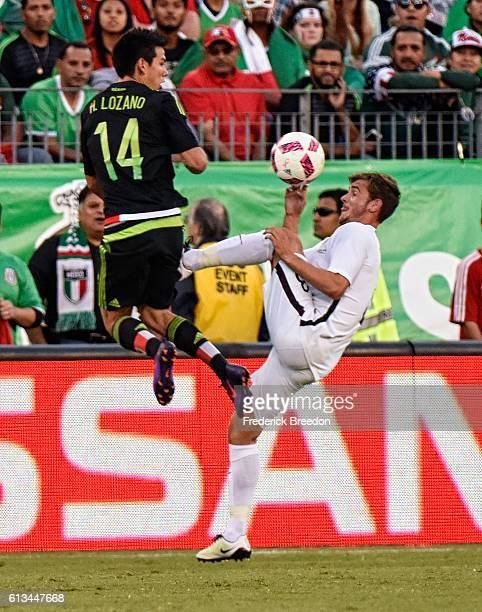 Hirving Lozano of Mexico and Michael McGlinchey of New Zealand collide chasing a ball during the first half at Nissan Stadium on October 8 2016 in...