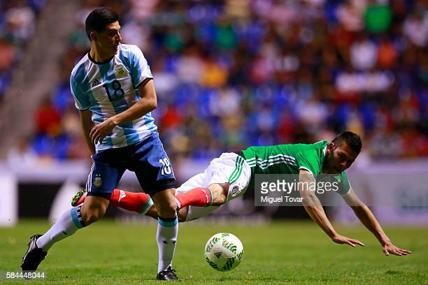 Hirving Lozano of Mexico falls down while fighting for the ball with Cristian Espinoza of Argentina during an U23 International Friendly between...