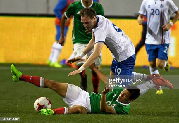Hirving Lozano of Mexico slides under Aron Elis Thrandarson of Iceland during their exhibition match at Sam Boyd Stadium on February 8 2017 in Las...