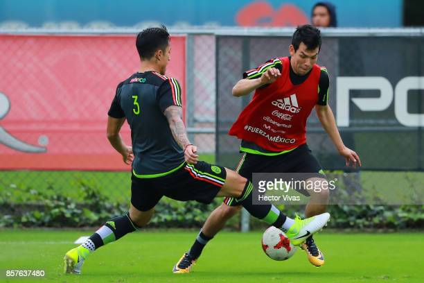 Hirving Lozano of Mexico struggles for the ball with teammate Carlos Salcedo during a Mexico's National Team training session ahead of the Qualifier...