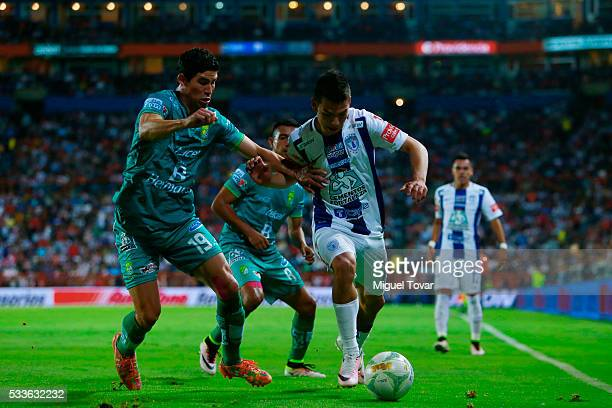 Hirving Lozano of Pachuca fights for the ball with Jose Magallon of Leon during the semi finals first leg match between Pachuca and Leon as part of...