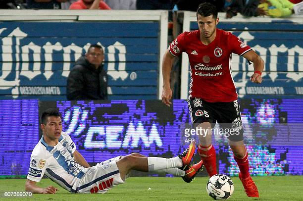 Hirving Lozano of Pachuca vies for the ball with Guido Rodriguez of Tijuana during their Mexican Clausura 2016 Tournament football match at Hidalgo...