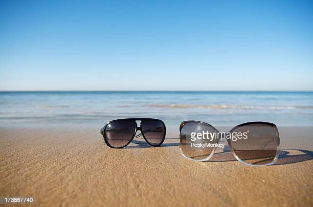 His and Hers Sunglasses on Empty Beach
