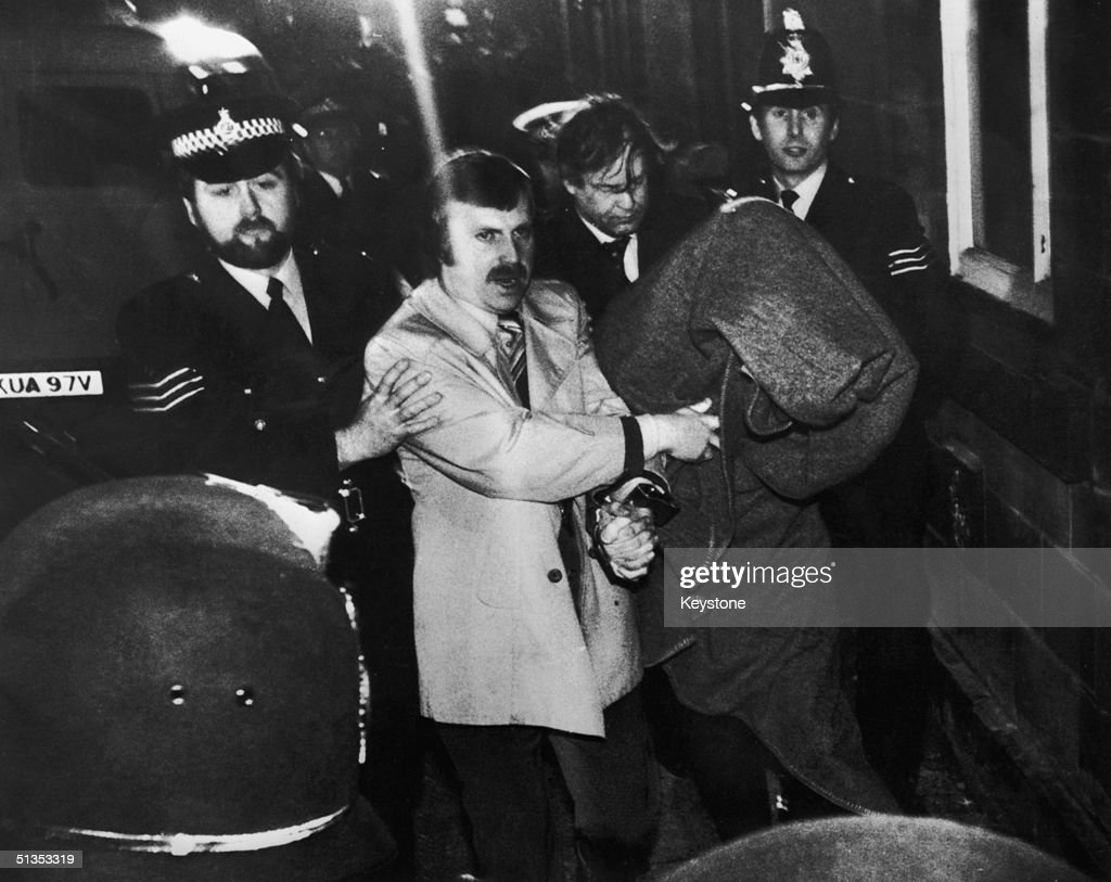 His head covered with a blanket, Peter Sutcliffe, aka 'The Yorkshire Ripper', is escorted into Dewsbury Magistrates Court to be charged with murder, 6th January 1981.