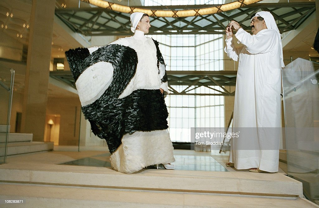 His Highness the Emir Sheikh Hamad bin Khalifa Al Thani photographs his wife Sheikha Mozah bint Nasser al-Missned inside the new Museum of Islamic Art in Doha, Qatar. She is wearing an haute-couture dress created by Hassan Bin Mohammed Bin Ali Al-Thani who was inspired by traditional Qatari dress. The design includes elements of the local cultural environment and the use of falcon feathers symbolizing superiority and liberty. Qatar's huge oil and gas reserves have made it one of the world's richest economies and has fuelled booming business, educational and cultural development.