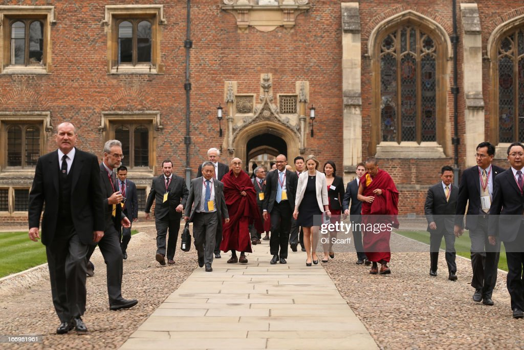 His Holiness the Dalai Lama (C) arrives to attend a press conference in the Divinity School of St. John's College, part of the University of Cambridge, on April 19, 2013 in Cambridge, England. The Dalai Lama was invited to address an audience in St. John's College by the Global Scholars Symposium during his 5-day visit to the UK. The exiled 77 year-old Buddhist Tibetan leader spoke on themes of non-violence, compassion, dialogue and universal responsibility.