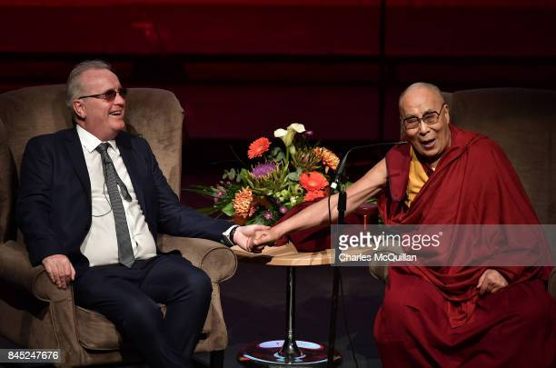 His Holiness The Dalai Lama holds the hand of Richard Moore as he gives a public talk on the theme of 'Compassion in Action' to celebrate 20 years of...