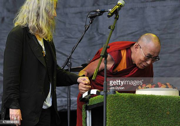 His holiness the Dalai Lama is presented with a cake for his forthcoming 80th birthday on the Pyramid stage during the third day of Glastonbury...