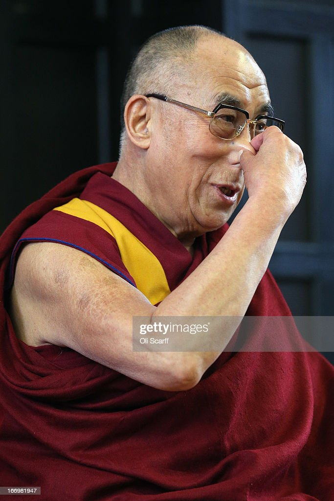 His Holiness the Dalai Lama pulls on his nose during a press conference in the Divinity School of St. John's College, part of the University of Cambridge, on April 19, 2013 in Cambridge, England. The Dalai Lama was invited to address an audience in St. John's College by the Global Scholars Symposium during his 5-day visit to the UK. The exiled 77 year-old Buddhist Tibetan leader spoke on themes of non-violence, compassion, dialogue and universal responsibility.