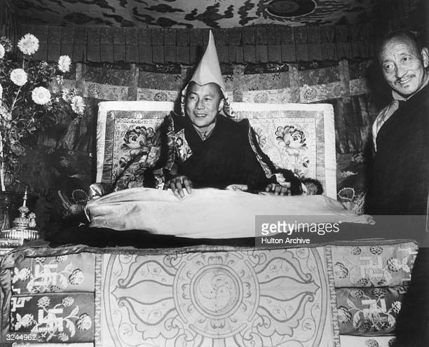 His Holiness the Dalai Lama Tenzin Gyatso seated on his throne and wearing the gold peaked cap which is his Crown smiles while giving an audience in...