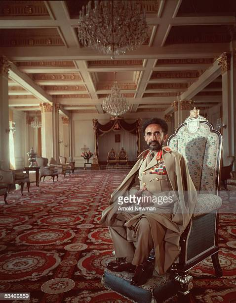 His Imperial Majesty Emperor Haile Selassie I sits on a throne in a grand room with an ornate carpet and vaulted ceiling adorned with chandeliers...