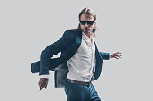 Handsome young man in full suit and sunglasses moving in front of grey background
