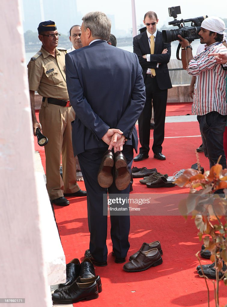 His personnel holds his shoes outside while Prince Charles paid tribute to Pir Baba inside Haji Ali Dargah, Mahalaxmi on November 11, 2013 in Mumbai, India. Haji Ali shrine is the resting abode of the Muslim saint Pir Haji Ali Shah Bukhari and is situated a few hundred meters ahead of the shoreline of the Arabian Sea. Prince Charles is on a nine-day-visit to the country with his wife, the Duchess of Cornwall, Camilla before leaving for Sri Lanka to attend the Commonwealth Heads of Government Meeting in Colombo.