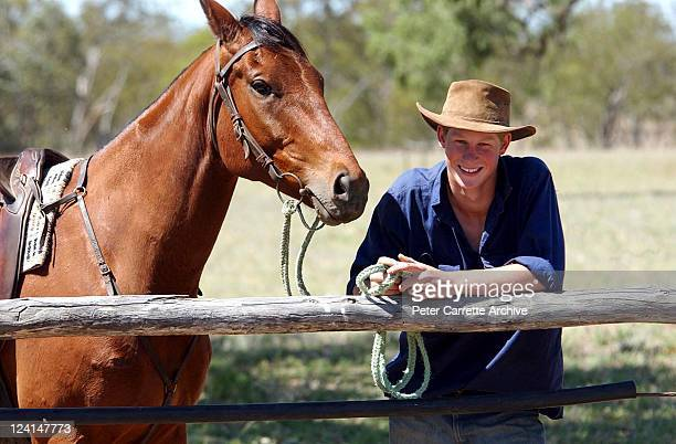 His Royal Highness Prince Harry poses for photographs with his horse 'Guardsman' after herding bulls while working as a Jackaroo on a cattle ranch on...