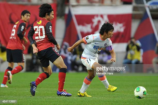 Hisato Sato of Sanfrecce Hiroshima and Gaku Shibasaki of Kashima Antlers compete for the ball during the JLeague match between Kashima Antlers and...